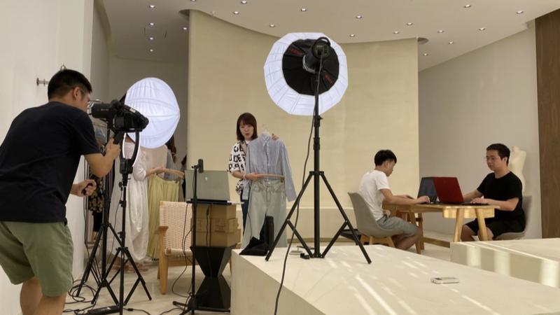 Yan Ke (C), a livestreamer on Taobao Live, works at Changshu Garments Town in Changshu, east China's Jiangsu Province, Aug. 17, 2020. (Xinhua)