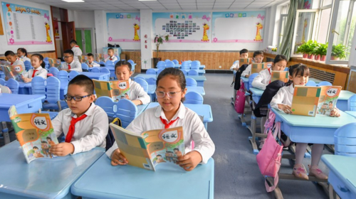 Primary students read in the morning session at a school in Changchun, Jilin Province, Aug. 23, 2021.